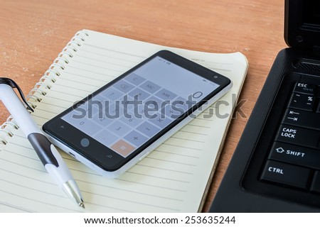 Office desk notebook pen and calculator - stock photo