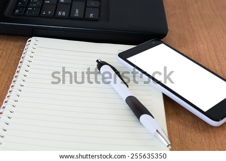 Office desk pen notebook and smart phone - stock photo