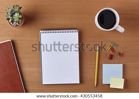 Office Desk Table with a Blank Notebook, Plant Pot, Cup of coffee, Pencil, Piece of Paper and Supplies. Workplace Top View on a Wooden Background with Copy space for text or Image - stock photo