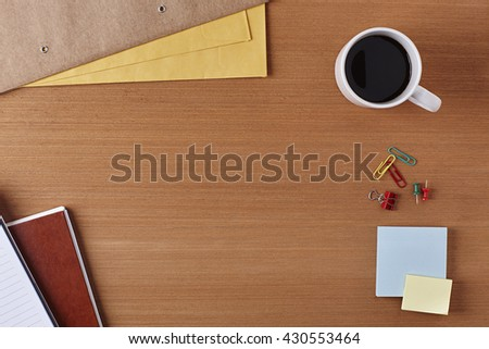 Office Desk Table with a Notebook, Cup of coffee, Envelop, Piece of Paper and Supplies. Workplace Top View on a Wooden Background with Copy space for text or Image - stock photo