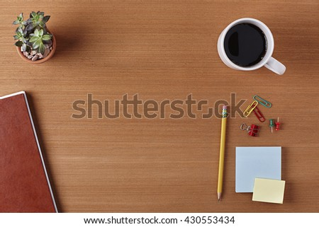 Office Desk Table with a Notebook, Plant Pot, Cup of coffee, Pencil, Piece of Paper and Supplies. Workplace Top View on a Wooden Background with Copy space for text or Image - stock photo