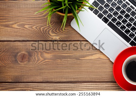 Office desk table with laptop computer, coffee cup and flower. Top view with copy space - stock photo
