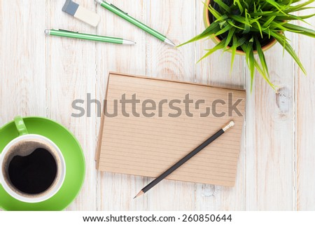 Office desk table with supplies, coffee cup and flower. Top view with copy space  - stock photo