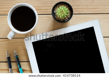 Office desk with blank screen tablet,pen,pencil and coffee cup on rustic wood table.Flat lay photo.Top view - stock photo