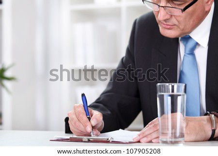Office desk with business man signing a contract. - stock photo