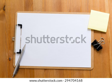 Office desk with clipboard showing a blank paper for advertising - stock photo