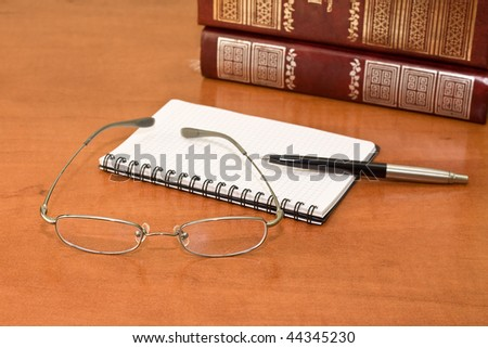 Office desk with glasses, books, pen and notepad