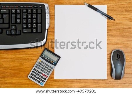 Office desk with keyboard, calculator, mouse, pen and a blank paper - stock photo