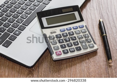 Office desk with laptop computer, calculator and  pen  on wooden background