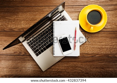 Office desk with laptop computer, notebook, mobile smartphone and coffee cup.  - stock photo