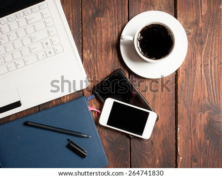 Office desk with laptop computer, notebook, mobile smartphone and coffee cup on wood - stock photo