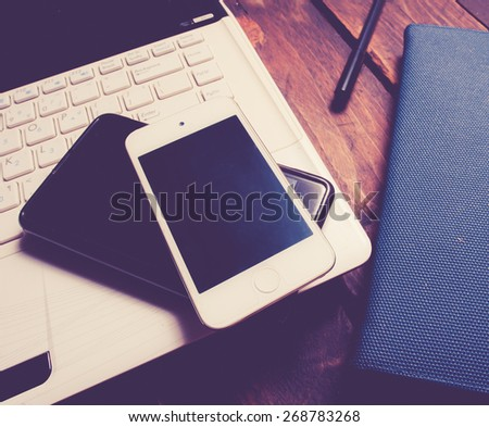 Office desk with laptop computer, notebook, mobile smartphone and pen on wood,vintage color toned image - stock photo