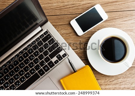 Office desk with laptop computer, planner, mobile smartphone and coffee cup.  - stock photo