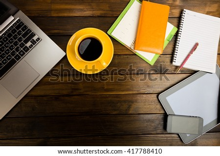 Office desk with laptop computer, tablet pc, planner, pen, mobile smartphone and coffee cup