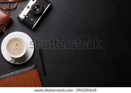 Office desk with photo camera, coffee and notepad. Top view with copy space - stock photo