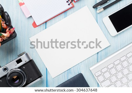 Office desk with supplies, camera and blank card. Top view with copy space - stock photo