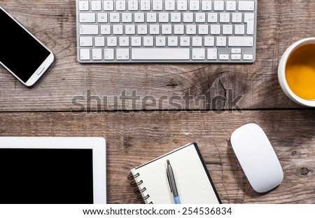 office desk with tablet , mobile phone , keyboard , mouse and tea - stock photo