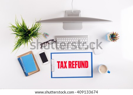 Office desk with TAX REFUND paperwork and other objects around, top view - stock photo