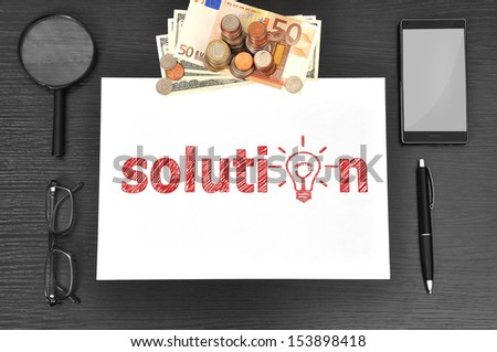 Office desktop, paper with solution and money - stock photo