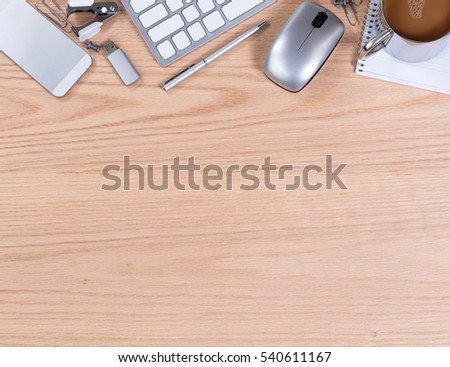 Office desktop with computer keyboard, mouse, coffee, thumb drive, pen, paper, clip, staple remover, and cell phone. Horizontal format with plenty of copy space