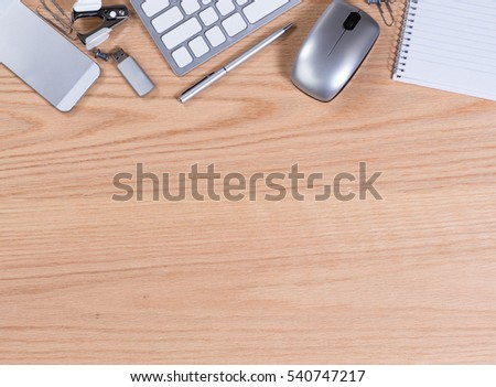 Office desktop with computer keyboard, mouse, thumb drive, pen, paper, clip, staple remover, and cell phone