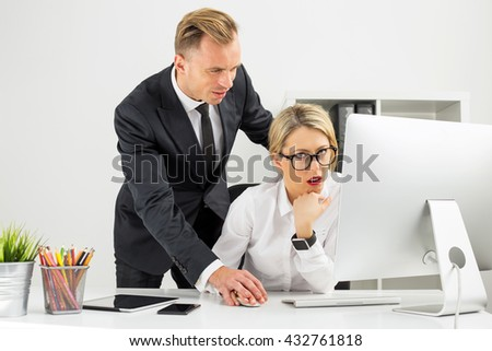 Office employee being annoyed by her boss - stock photo