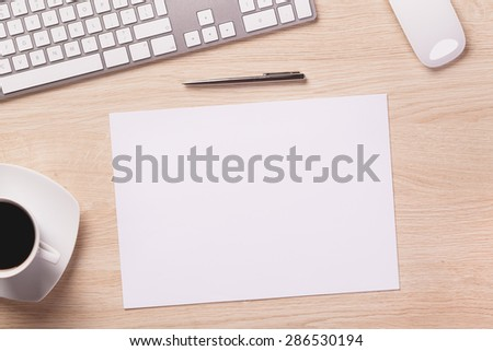 Office equipment such as computer keyboard, mouse, sheet of paper and pen on office wooden desk with coffee. - stock photo