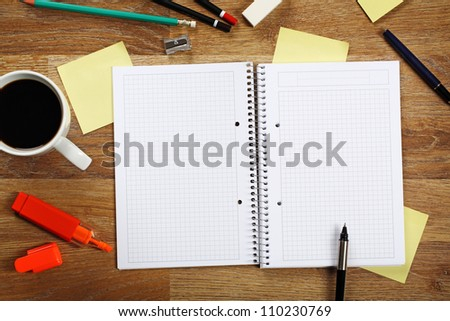 Office equipment such as opened notebook, pen, highlighter, cup of coffee, pencil, sticky notes and other on bright wooden office desk.