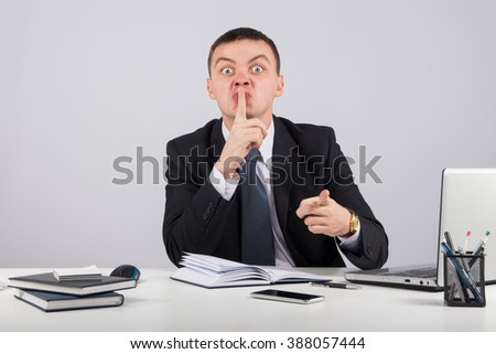Office, finances, internet, business, success and people concept-Businessman holding his finger in front of his mouth and making silence gesture shh - stock photo