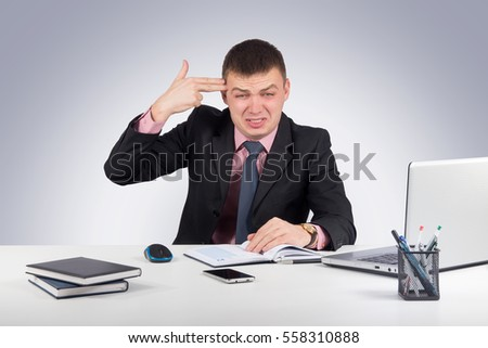 Office, finances, internet, business, success and stress concept-Frustrated businessman despair pointing his finger to his head like shooting a gun