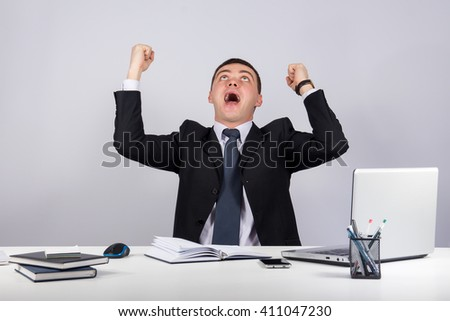 Office, finances, internet, business, success concept-happy young  businessman with his arms raised up on gray background - stock photo
