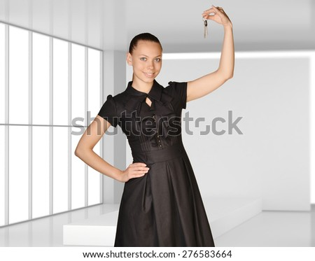 Office girl standing on background of light interior house and is holding keys. - stock photo
