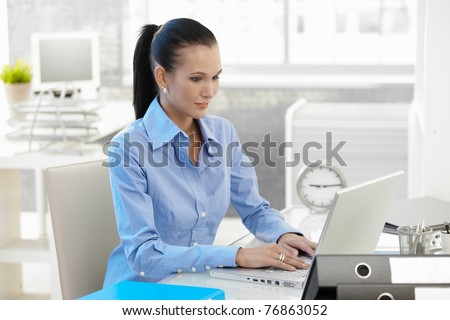 Office girl working on laptop computer at desk, looking at monitor, smiling.?