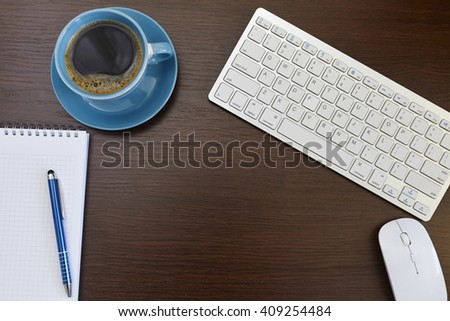 Office leather desk table with computer, supplies and coffee cup.