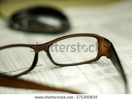 Office life,closeup of a glasses on a newspaper with a very shallow depth of field with copy space for text - stock photo