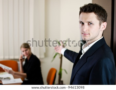 Office life scene. Young businessman invites to his office.