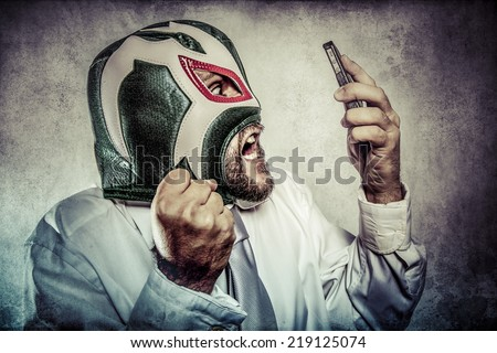 Office man arguing by phone, aggressive executive suit and tie, Mexican wrestler mask - stock photo