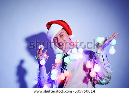 Office man in a Santa Claus red cap with colored garlands