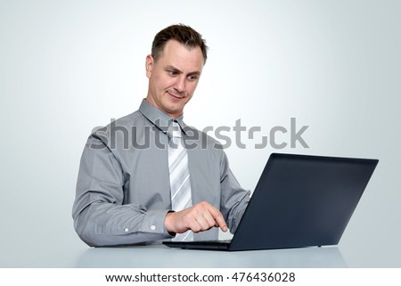 Office man in shirt and tie with laptop on background