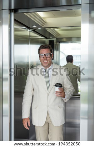 Office manager going out of elevator - stock photo