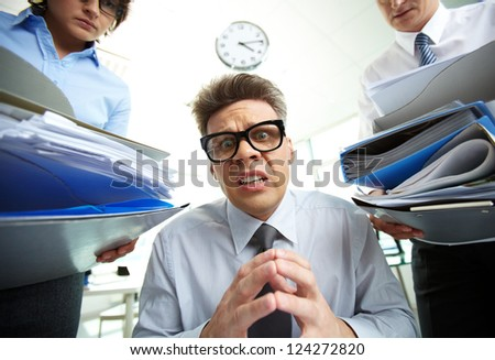 Office manager panicking because of piles of documentation - stock photo