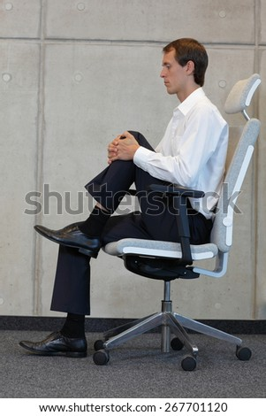 office occupational disease prevention -business man exercising on chair - profile view - stock photo
