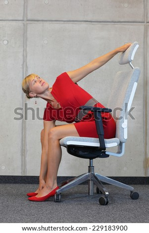 office occupational disease prevention - business woman exercising on chair - stock photo
