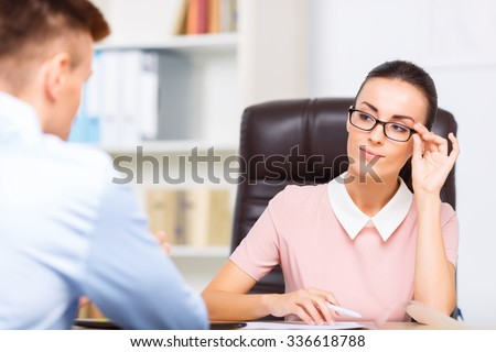 Office ogling. Female attractive executive sits at her desk while ogling her partner.