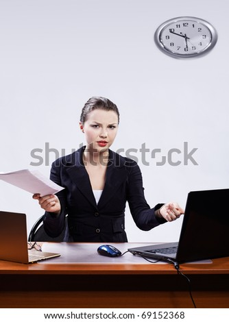 office portrait of beautiful dissatisfied business woman at her workplace with documents and two laptops on gray
