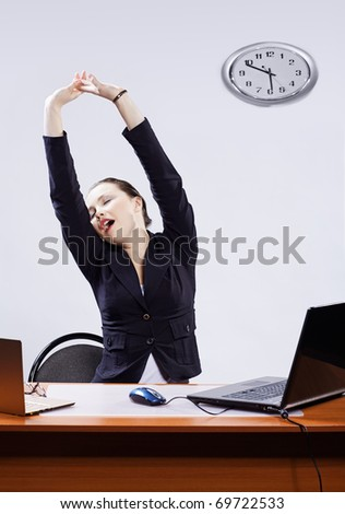 office portrait of beautiful tired business woman stretching and yawning at her workplace with two laptops on gray - stock photo