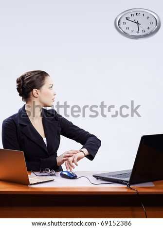 office portrait of beautiful young business woman sitting at her workplace with two laptops on gray and regulating her watches with clocks on wall