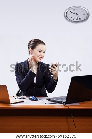 office portrait of beautiful young business woman sitting at her workplace with two laptops on gray checking makeup