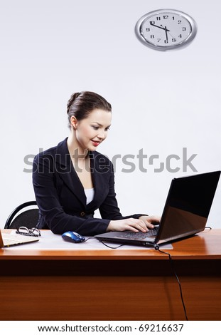 office portrait of beautiful young business woman sitting at her workplace with two laptops on gray