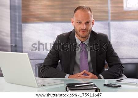 Office portrait of handsome businessman sitting at desk, looking at camera.